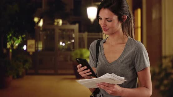 Thumbnail for Woman with mail checking smartphone and walking offscreen in outdoor courtyard