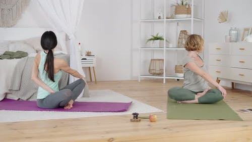 Yoga Instructor and Client Stretching Body During Home Practice