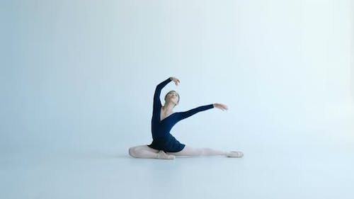 Young Ballet Dancer Sits Half-twine Moving Hands in Dance