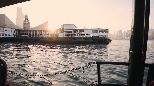 Star Ferry Pier At Tsim Sha Tsui With Clock Tower And Bright Sunset On The Background In Hong Kong.