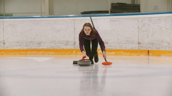 Thumbnail for Curling - a Woman in Glasses Skating on the Ice Field and Leading a Granite Stone