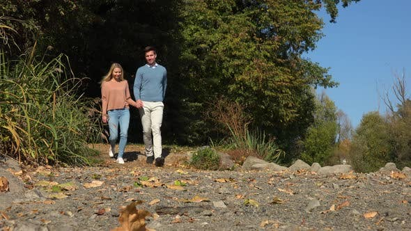 Thumbnail for A Young Attractive Couple Walks Down a Path in a Park, Stops at the Edge of Slope and Looks at View