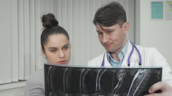 Doctor and Patient Looking at MRI Scan on Medical Appointment