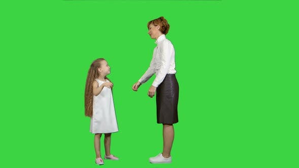 Thumbnail for Beautiful Mother and Daughter Giving High Five and Smiling Each Other on a Green Screen, Chroma Key