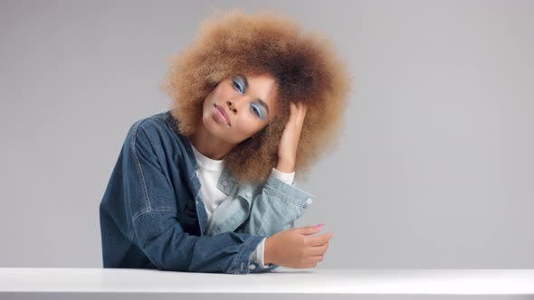 Mixed Race Black Woman with Big Afro Hair in Studio Alone in Denim Shirt