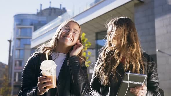 Thumbnail for Two Young Caucasian Women Using Digital Tablet and Smiling Happily while Walking in City