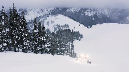 Snowcat Grooming Slope At Ski Resort At Dusk Aerial Overview