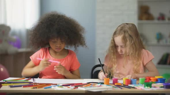 Thumbnail for Early education, two multi-ethnic female kids drawing with colorful pencils