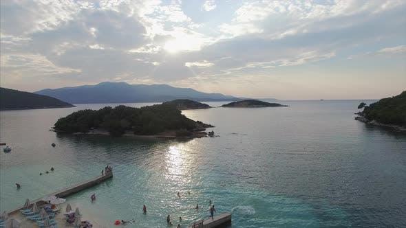 Dock on beach with people enjoying Albania