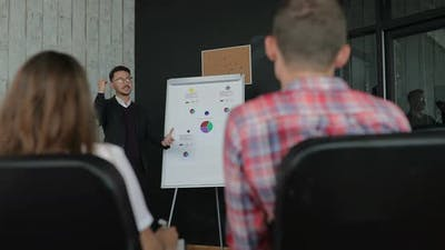 Businessman Giving a Presentation to Colleagues in the Office