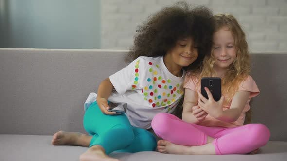 Thumbnail for Multiracial Sisters Sitting on Sofa and Taking Selfie on Smartphone at Home