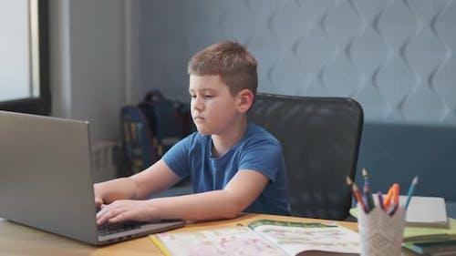 Porträt eines kleinen Jungen, der online Unterricht in der Ferne über Laptop und Internet per Video unterrichtet