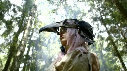 Crazy Savage Female Witch Is Moving in Forest in Daytime, View on Her Face with Mask