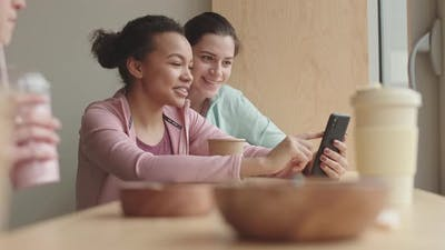 Female Friends Using Smartphone in Cafe