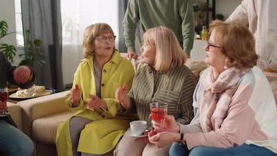 Cheerful Elderly Women Chatting at Home Party