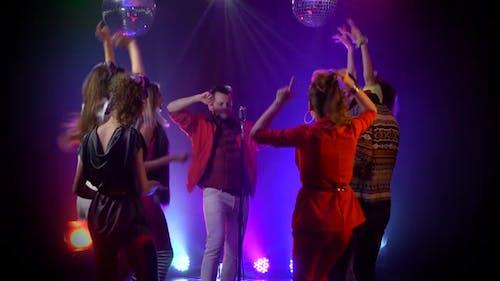 Mann singt in ein Retro Mikrofon um Menschen tanzen zu singen