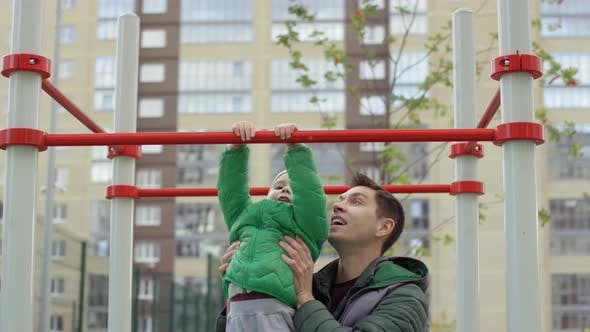 Cover Image for Young Man Helping Son Do Pull-Ups at Playground