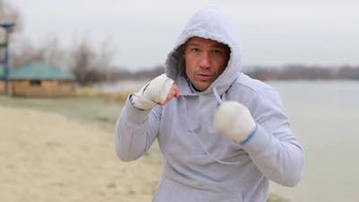 Boxing a man with an invisible opponent. A young man trains outdoors.