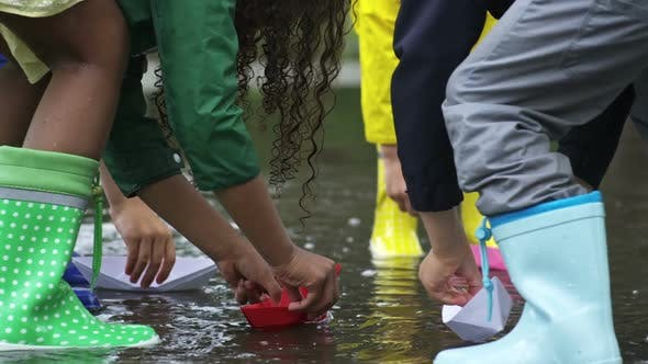 Cover Image for Children Putting Paper Boats in Puddle
