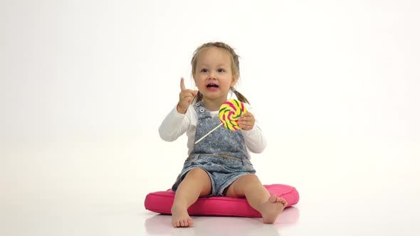 Thumbnail for Little Girl Is Holding a Sweet Candy in Her Hands and Licks It. White Background