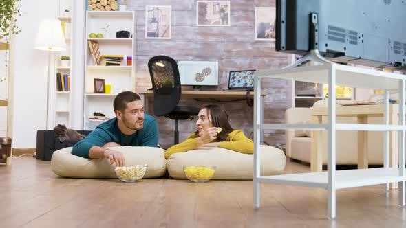 Cover Image for Couple Talking with Each Other Watching Tv Sitting on the Pillows for the Floor