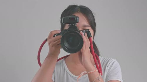 Young Asian Female Photographer Standing And Taking Photos In Studio