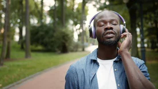 Thumbnail for Afro-american Male in Headphones Singing in Park