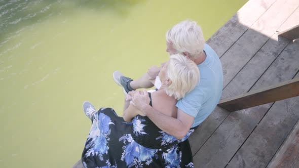 Thumbnail for Top View of a Happy Mature Couple Sitting on the Bench Near the River, Admiring Nature