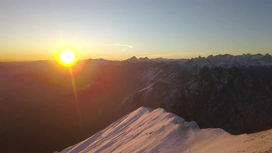 Thumbnail for Aerial drone view of snow covered Alps mountains in the winter at sunset