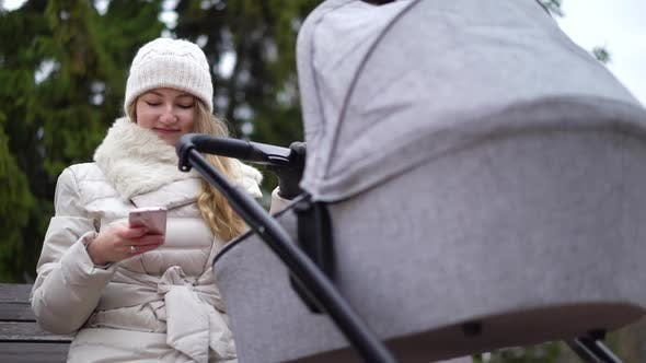 Thumbnail for Glückliche Mutter mit Smartphone mit App. Sie sitzt auf der Bank, Baby schlafen in Kinderwagen