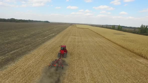 Thumbnail for Farmer in Red Tractor Preparing Land for Sowing, Aerial Shot