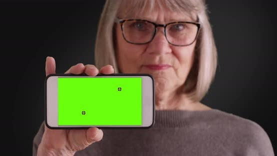 Thumbnail for Elderly white woman holding up phone with green screen on gray background