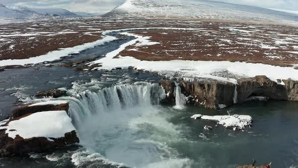 Aerial View of Godafoss Waterfall with Snowy Shore and Ice. Iceland. Winter 2019