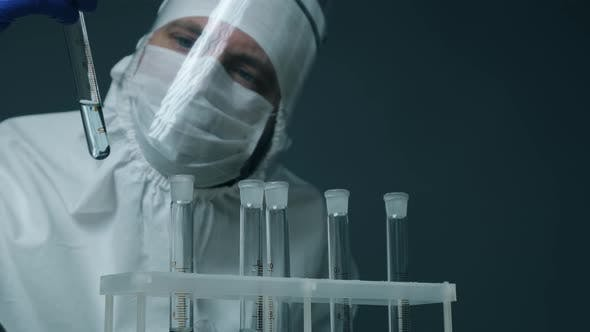 Scientist or Doctor in Protective Kit Holding Test Tube with Reagent. Laboratory Glassware