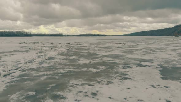 Aerial Motion Over Frozen River with Snow Under Cloudy Sky