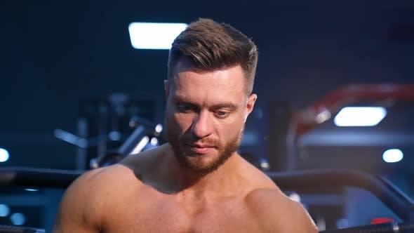 Gut aussehender Mann mit großen Muskeln, der im Fitnessstudio auf die Kamera posiert.