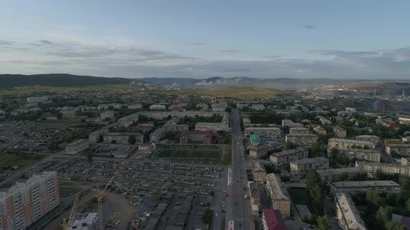 Thumbnail for Aerial view of city with hight and low buildings. Cars are driving
