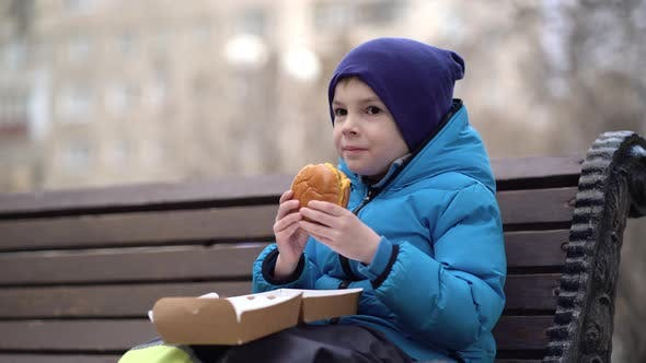 Hungry Kid Eating Double Cheeseburger Outdoor