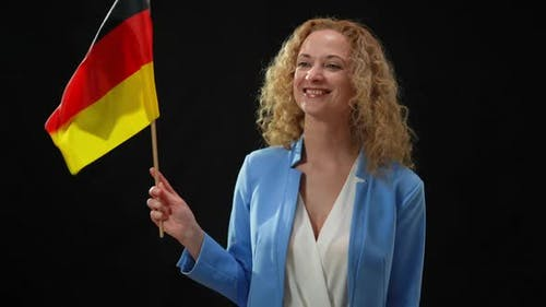 Portrait of Charming Confident Politician Holding German Flag Waving Looking Around in Camera