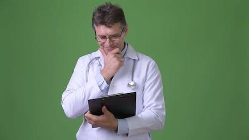 Mature Handsome Man Doctor Against Green Background