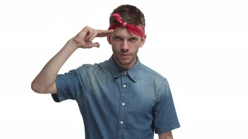Sassy Handsome Guy with Beard Red Bandana Over Forehead Making Finger Gun Sign Over Head and