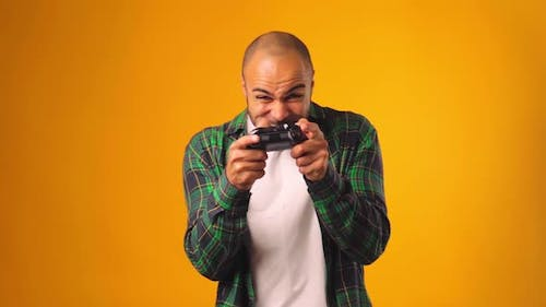 Young African American Man Playing Video Games with Joystick in Hands Against Yellow Background