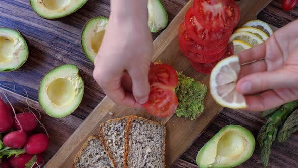 Thumbnail for Healthy Vegan Breakfast Concept. Making Avocado Toast With Lemon And Tomato.