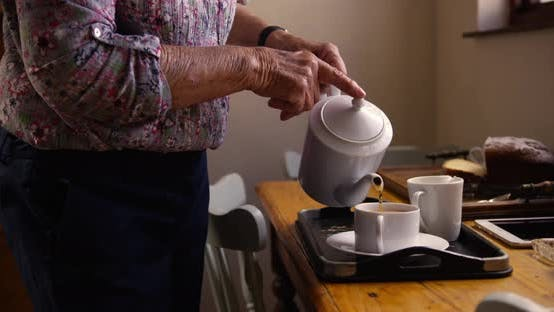 Thumbnail for Woman preparing coffee on dining table in kitchen at home 4k