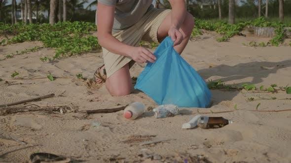 Freiwillige Mann pflücken Müll am Strand