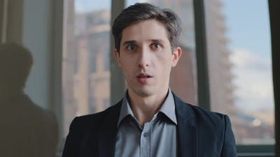Portrait of Caucasian Millennial Scared Business Man Shocked Employee Sitting in Office Shaking
