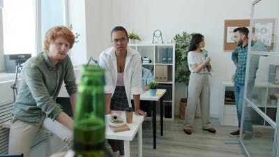 Closeup of Alcohol Bottle and Employees Looking at It with Blame and Disappointment
