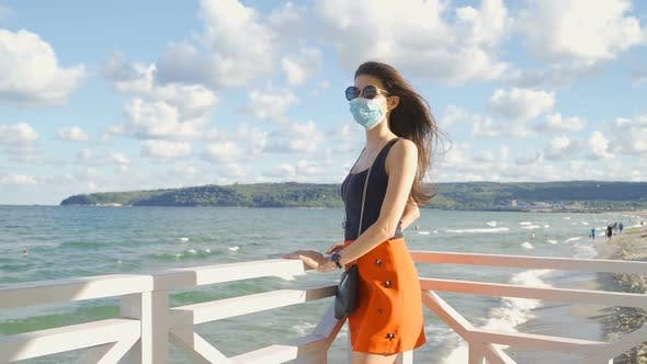 Thumbnail for Fit Woman with Sunglasses and Face Mask Looking Over a Fence at the Sea. Protection Measures During