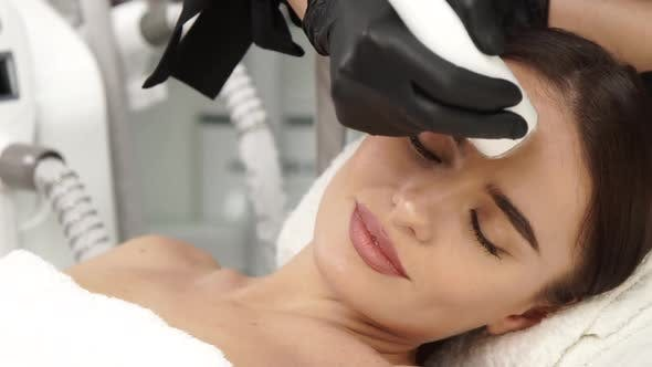 Beautiful Female Receiving Facial Treatment with Beauty Shape at Spa Salon