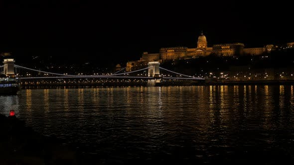 Beautiful lighted Szechenyi  Bridge and royal palace on Buda hill  by night 4K 2160p UltraHD footage
